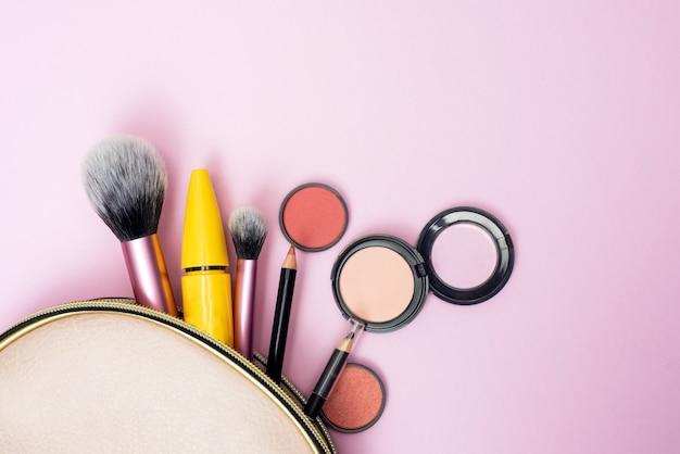 Produkty do makijażu wysypujące się z różowej kosmetyczki