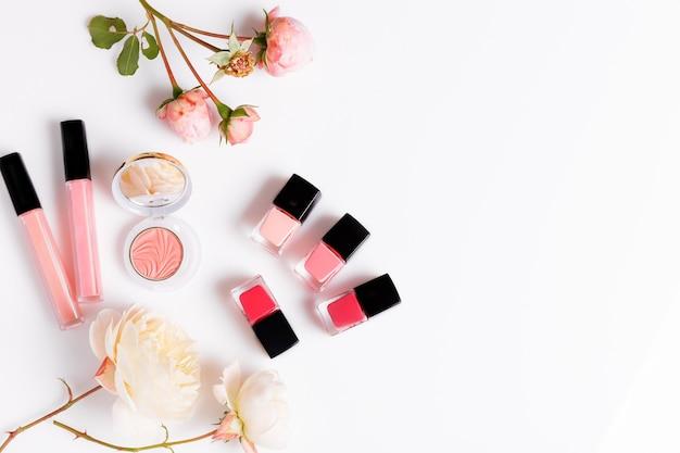 Produkty do makijażu z różową angielską różą na jasnym tle. beauty flat leżała z butelkami kosmetycznymi i kwiatami.