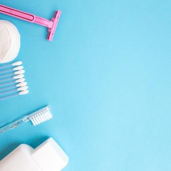 Produkty do pielęgnacji ciała. biała butelka, brzytwa, paluszki uszne, bawełniane podkładki, szczoteczka do zębów na niebiesko
