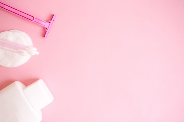 Produkty do pielęgnacji ciała. biała butelka, brzytwa, paluszki uszne, waciki na różowym tle. do