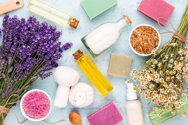 Produkty do pielęgnacji i bukiet świeżej lawendy na białym drewnianym stole.