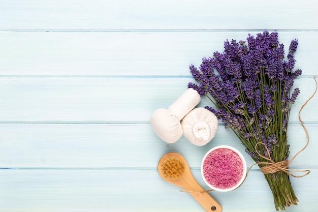 Produkty do pielęgnacji i bukiet świeżej lawendy na tle biały drewniany stół.