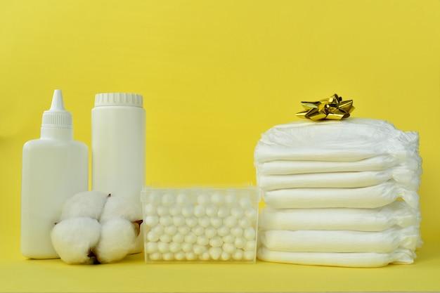 Produkty do pielęgnacji niemowląt na żółtym tle.