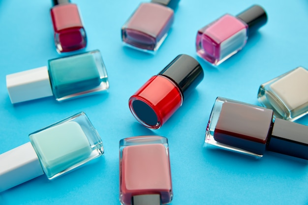 Produkty do pielęgnacji paznokci, lakiery w butelkach na niebieskim stole. koncepcja procedur opieki zdrowotnej, kosmetyki modowe, narzędzia do manicure i pedicure, lakier do paznokci