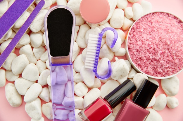 Produkty do pielęgnacji paznokci na kamyczkach, kolorowy lakier w butelkach na różowym stole. koncepcja procedur opieki zdrowotnej, kosmetyki modowe, narzędzia do manicure i pedicure, lakier do paznokci