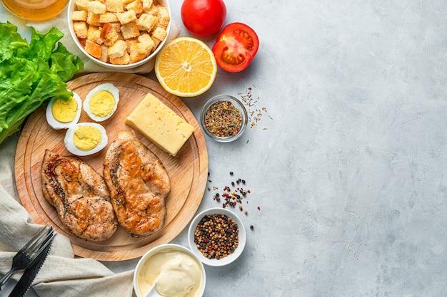 Produkty do przygotowania tradycyjnej sałatki cezar. soczysta pierś z kurczaka, jajka, ser, sos i zioła na szarym tle. widok z góry z miejscem na kopię.