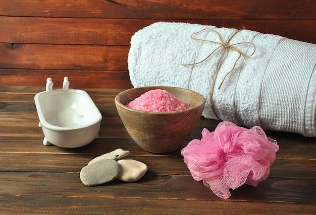 Produkty do spa i pielęgnacji ciała. aromatyczna róża kąpiel morza martwego sól na ciemnym tle drewniane. naturalne składniki domowego peelingu solnego do ciała. kosmetyki z morza martwego.