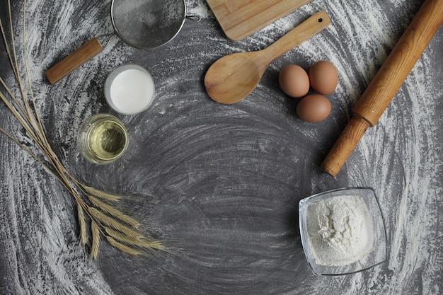 Produkty do wypieku chleba i ciasta na stole z szarego betonu jajko kurze, mąka, oliwa z oliwek i mleko.
