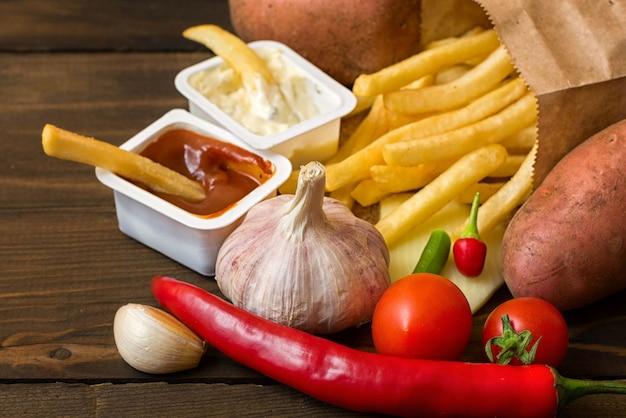 Produkty fast food: frytki z sosem i składniki żywności na ciemnym drewnianym stole, widok z góry