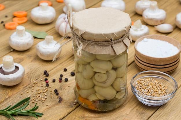 Produkty fermentacji. szklany słoik z grzybami konserwowymi i świeżymi pieczarkami. przyprawa: sól, czosnek, cebula, liść laurowy na stole. zdrowa żywność zimą, z bliska. jasna drewniana powierzchnia