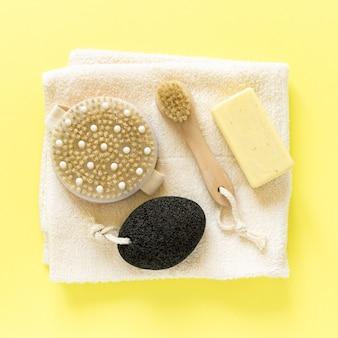 Produkty i artykuły do łazienki. pędzle do masażu, mydło, pumeks i ręcznik na żółtym tle, widok z góry.