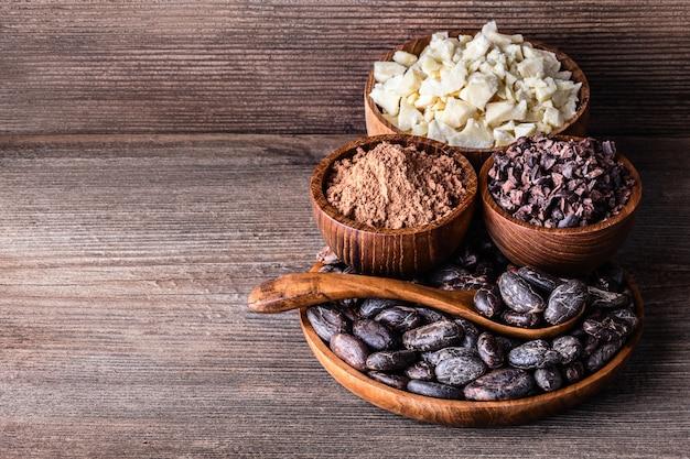 Produkty kakaowe w łyżkach drewniane miski na starym stole rustykalnym.
