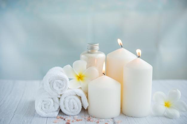 Produkty kokosowe spa na jasnej powierzchni drewnianej. kompozycja z ręcznikami, kwiatami i solą, świeca na stole do masażu w salonie spa