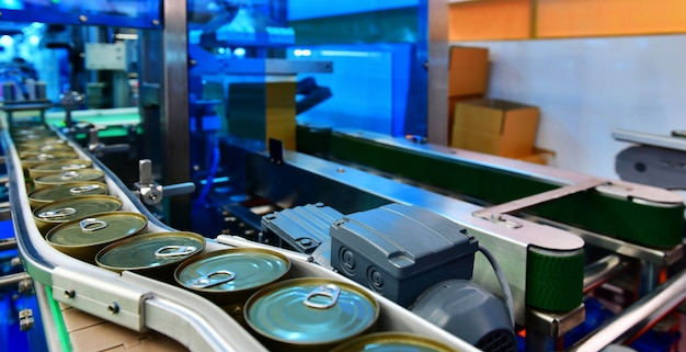 Produkty konserwowe na przenośniku taśmowym w magazynie dystrybucyjnym. koncepcja systemu transportu paczek.