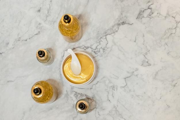 Produkty kosmetyczne, kosmetyki dekoracyjne na tle białego marmuru. blogerka modowa. produkty copyspace.spa i złoty kosmetyk hydrogel