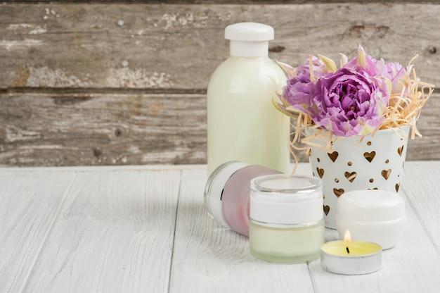 Produkty kosmetyczne, kosmetyki, zapalona świeca i fioletowe tulipany