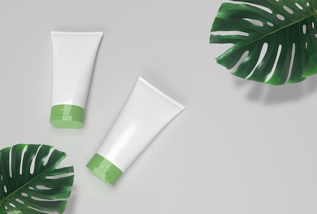 Produkty kosmetyczne spa na białym tle, białe tubki z zieloną pokrywką i tropikalnymi liśćmi.