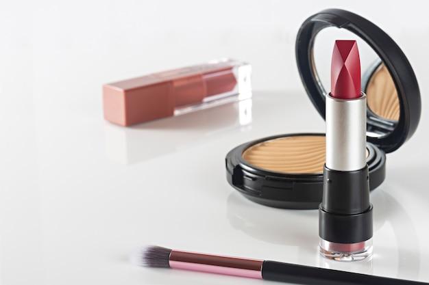 Produkty kosmetyczne szminka, proszek na białym stole.