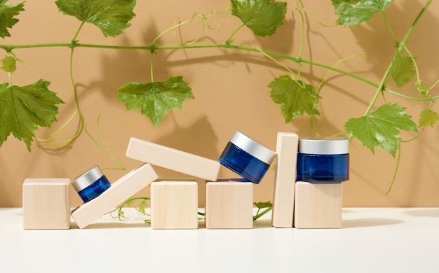 Produkty kosmetyczne w niebieskim szklanym słoju z szarą pokrywką stoją na drewnianym podium z kostek, za gałązką winogron z zielonymi liśćmi. puste miejsce do znakowania produktów, balsam na beżowym tle