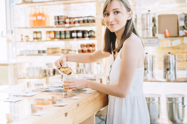 Produkty luzem w sklepie zero waste kobieta kupująca suche towary w sklepie spożywczym bez plastiku