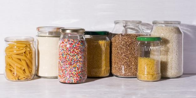 Produkty luzem w sklepie zero waste. płatki zbożowe i cukierki w szklanych słoikach na półkach. ekologiczne zakupy w sklepie spożywczym bez plastiku.