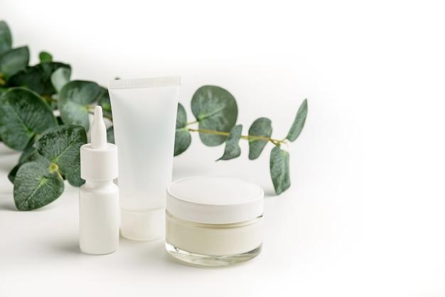 Produkty medyczne i kosmetyczne i gałąź eukaliptusa na białym tle.