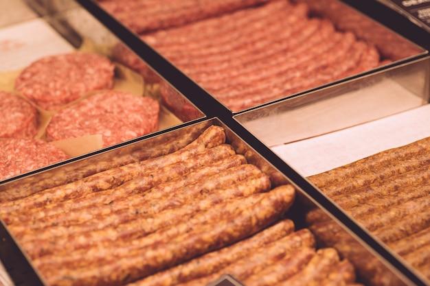 Produkty mięsne: klopsiki, kiełbasy, mięso mielone w oknie rynku mięsnego.