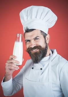 Produkty mleczne i koncepcja gotowania. zdrowa żywność na twój stół. uśmiechający się brodaty mężczyzna kucharz na sobie biały mundur o szklaną butelkę domowego świeżego mleka surowego. mężczyzna kucharz trzyma butelkę mleka, koktajl mleczny