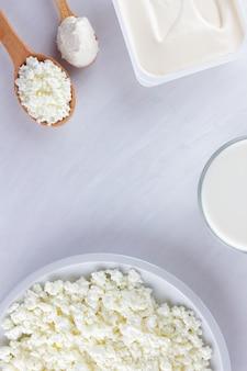 Produkty mleczne na białej tablicy. twarożek, śmietana i ser miękki na białym tle