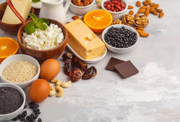 Produkty mleczne, rośliny strączkowe, jaja, orzechy, czekolada, mak, sezam, czekolada. białe tło, kopia przestrzeń