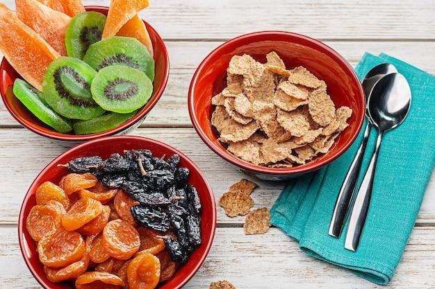 Produkty na zdrowe śniadanie. miski drewniane z orzechami, suszonymi owocami. płatki zbożowe z mlekiem.