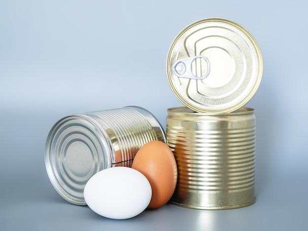 Produkty pierwszej potrzeby i długotrwałe przechowywanieec. konserwy i jajka na szarym tle, zbliżenie.