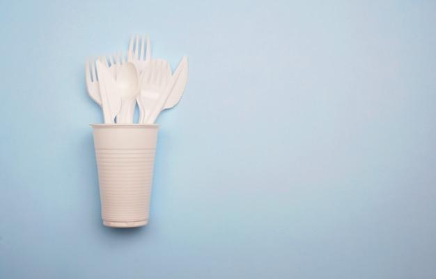 Produkty plastikowe jednorazowego użytku: plastikowe sztućce, kubki na jasnym niebieskim tle