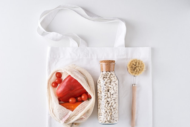 Produkty wielokrotnego użytku bez plastiku, koncepcja zero odpadów. świeże warzywa, fasola w szklanej butelce i tekstylna torba na zakupy