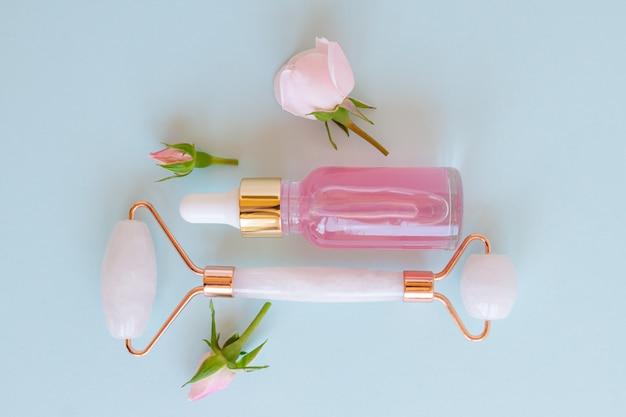 Produkty z olejkiem kosmetycznym quartz roller na niebieskim tle z pąkami róży. serum lub olej i narzędzia do pielęgnacji skóry. koncepcja odnowy biologicznej. widok z góry.