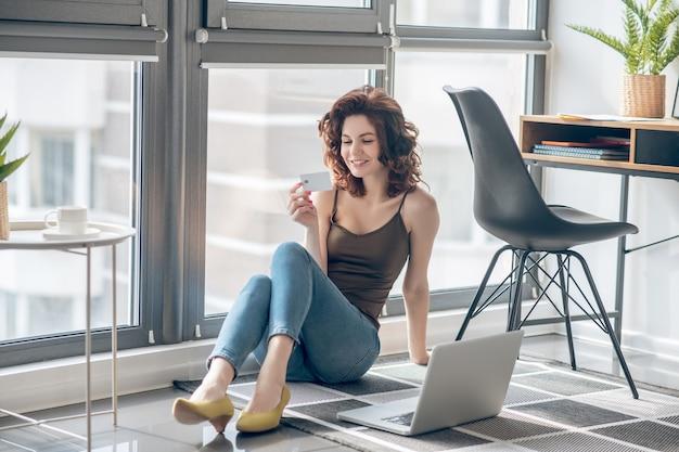 Produktywność. ciemnowłosa ładna kobieta pracuje na laptopie i wygląda na zadowoloną