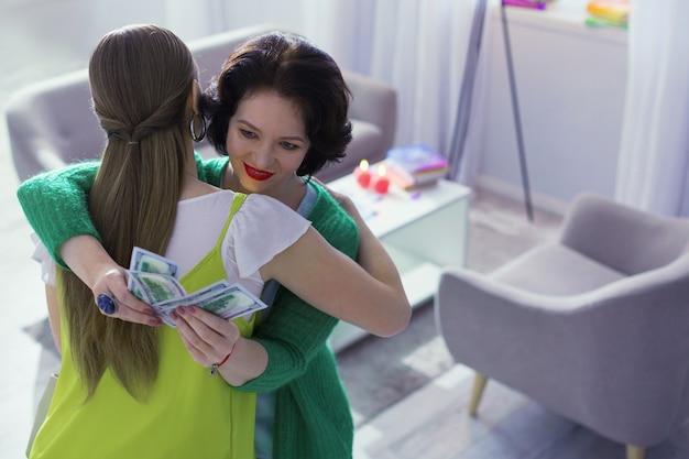 Produktywny dzień. zachwycona, szczęśliwa kobieta liczy pieniądze, przytulając gościa