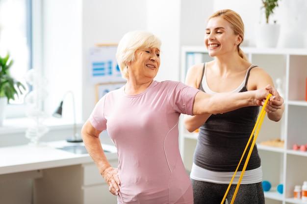 Produktywny trening. pozytywna starsza kobieta trenująca z gumką, chcąca rozwijać mięśnie
