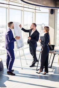 Profesjonaliści biznesowi. grupa młodych, odnoszących sukcesy ludzi biznesu analizuje dane za pomocą wykresów, spędzając czas w nowym, nowoczesnym biurze.