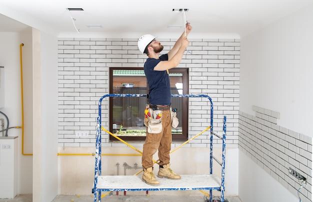 Profesjonalista w kombinezonie z narzędziami na miejscu naprawy na całej długości. koncepcja renowacji domu.