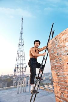 Profesjonalista w stylu vintage. bez koszuli, muskularny pracownik budowlany, odwracający wzrok, wspinający się po drabinie w słoneczny dzień pracy