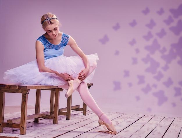 Profesjonalna baletnica zakładająca baletki na drewnianej podłodze