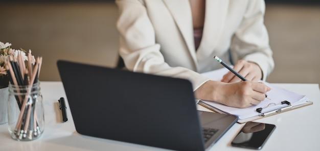 Profesjonalna bizneswoman pracuje nad swoim projektem podczas pisania informacji na dokumentach