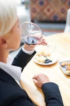 Profesjonalna dojrzała sommelierka degustuje czerwony cabernet z kieliszka do wina, oceniając jego smak