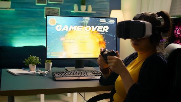 Profesjonalna gra wideo r przegrywająca kosmiczną strzelankę podczas noszenia zestawu słuchawkowego do rzeczywistości wirtualnej