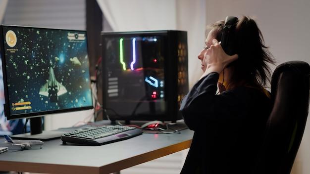 Profesjonalna grająca w e-sport kobieta przychodzi do pokoju gier, grając w kosmiczną strzelankę podczas mistrzostw online. streaming cyber występujący na potężnym komputerze podczas wirtualnego turnieju