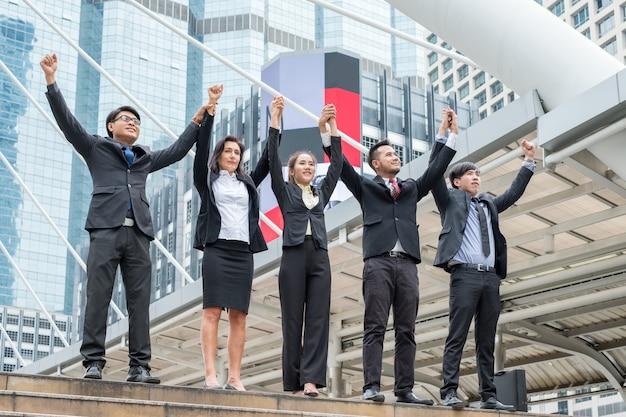 Profesjonalna grupa biznesowa z podniesionym ramieniem to szczęście z sukcesem