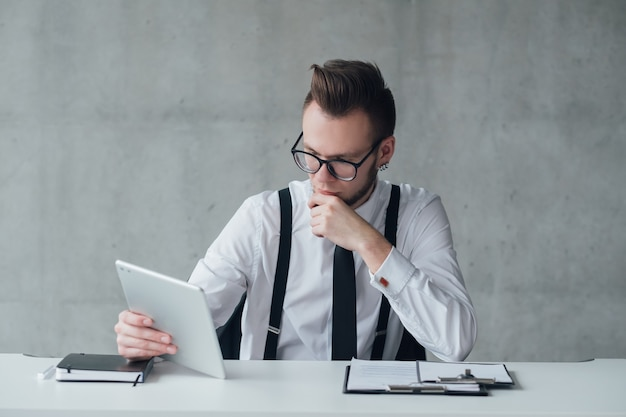 Profesjonalna kariera. nowoczesna firma. head hunter skupiony na czytaniu cv na tablecie.