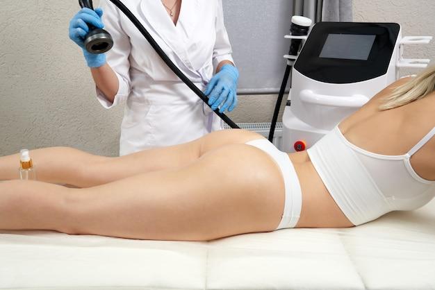 Profesjonalna kosmetolog używająca ultradźwiękowej maszyny do kawitacji na kobiecym pośladku