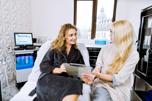 Profesjonalna kosmetologia i pielęgnacja skóry. młoda pozytywna kosmetyczka siedząca obok swojego klienta, ładna blond kobieta, patrząc na papier z informacjami o kosmetykach i skórze